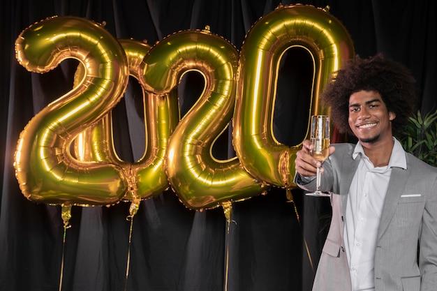 Homem segurando uma taça de champanhe e feliz ano novo 2020 balões