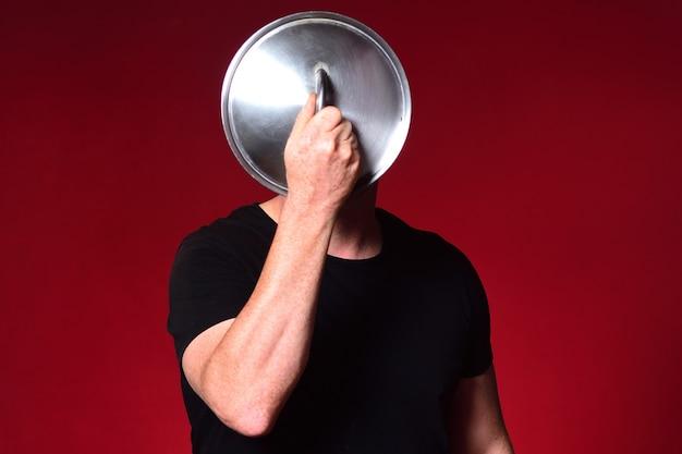 Homem segurando uma tampa de panela na frente do rosto
