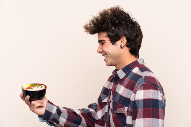 Homem segurando uma tigela cheia de macarrão com expressão feliz
