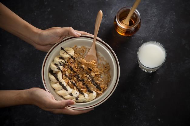 Homem segurando uma tigela com flocos de milho na mesa