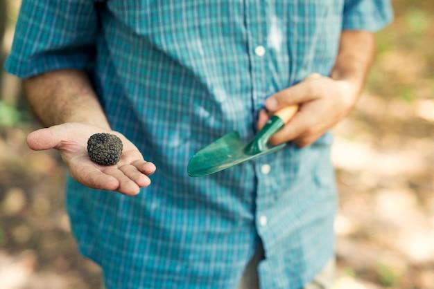 Homem segurando uma trufa negra com o polegar para cima na natureza