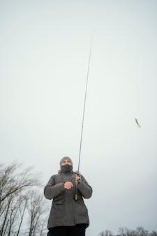Homem segurando uma vara de pescar