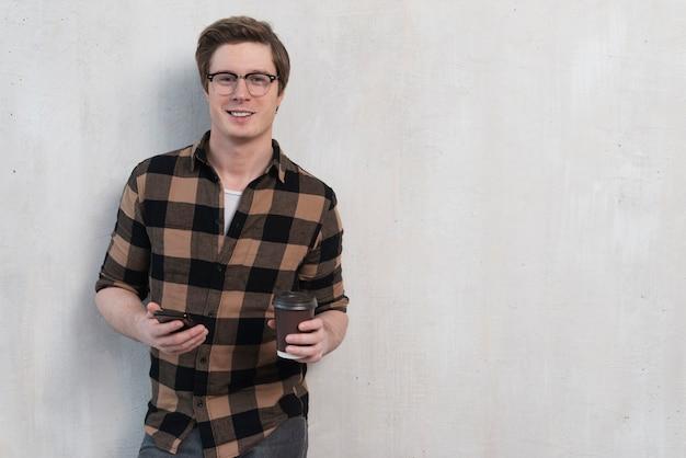 Homem segurando uma xícara de café com espaço de cópia