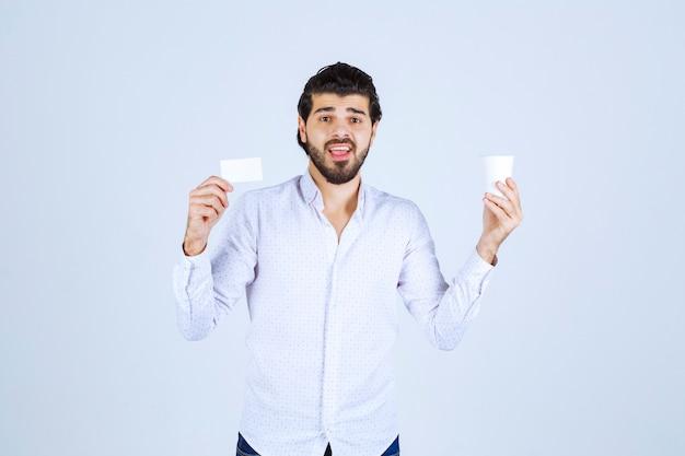 Homem segurando uma xícara de café com uma das mãos e apresentando seu cartão de visita com a outra