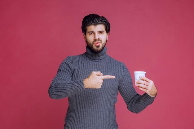 Homem segurando uma xícara de café descartável e apontando para ela.