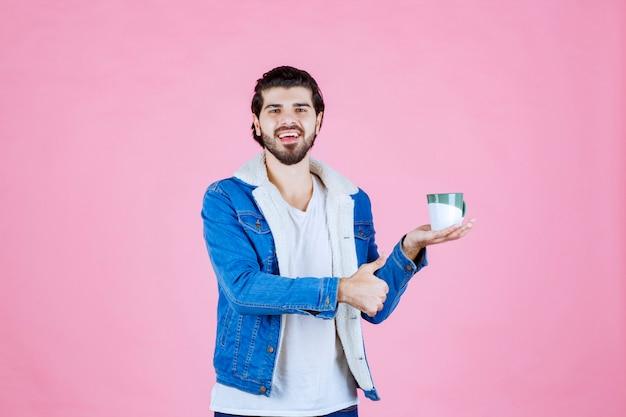 Homem segurando uma xícara de café e apreciando o sabor
