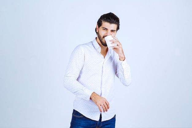 Homem segurando uma xícara de café e bebendo café enquanto posa