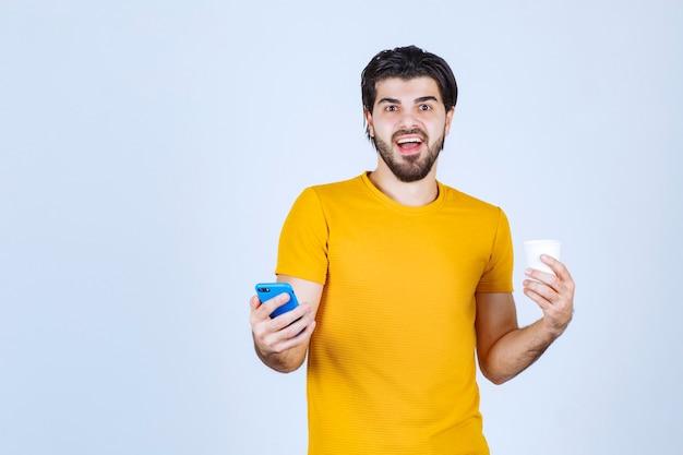 Homem segurando uma xícara de café e demonstrando seu novo modelo de smartphone.