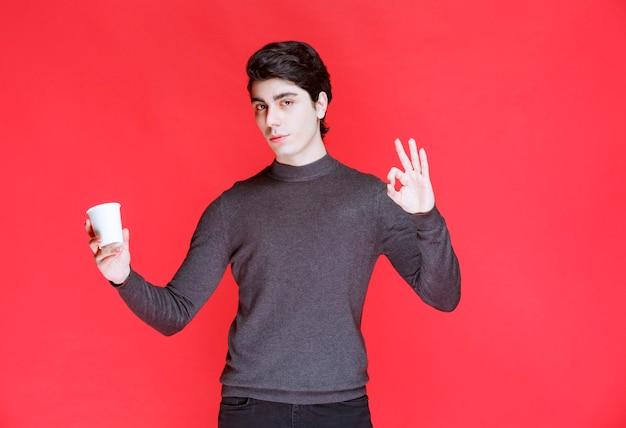 Homem segurando uma xícara de café e mostrando sinal positivo