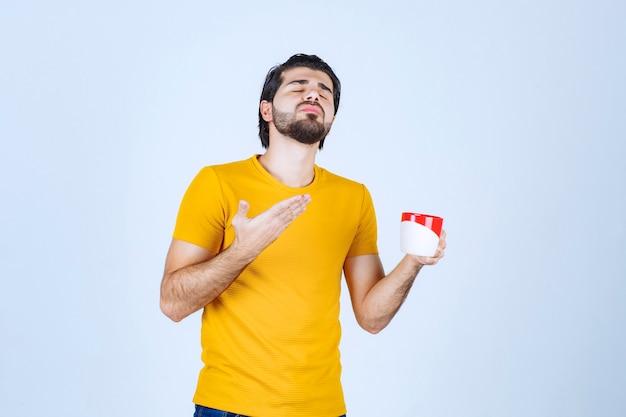 Homem segurando uma xícara de café e soprando o cheiro.