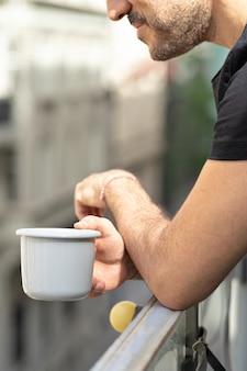 Homem segurando uma xícara de café na varanda com vista cidade