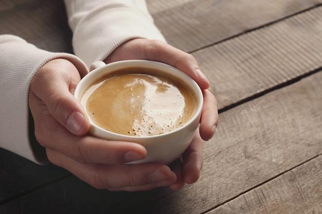 Homem segurando uma xícara de café nas mãos em uma superfície de madeira