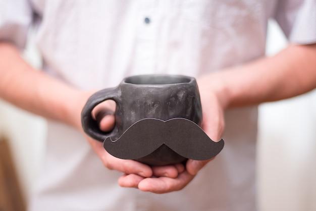 Homem segurando uma xícara de cerâmica preta