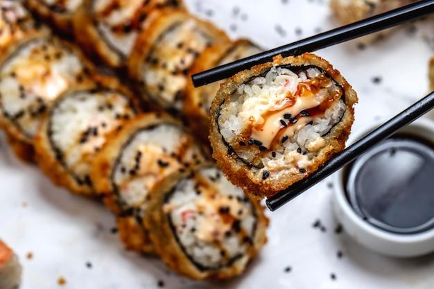 Homem segurando varas com tempura roll arroz caranguejo creme queijo gergelim enguia gengibre wasabi vista lateral
