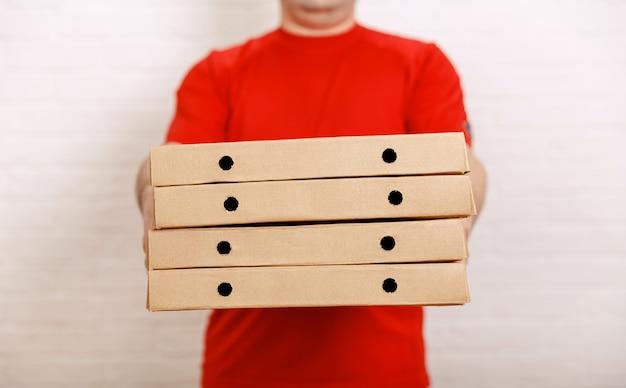 Homem segurando várias caixas de pizza entregando serviço de comida