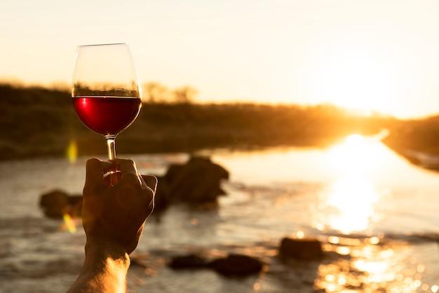 Homem, segurando, vidro vinho, em, a, natureza