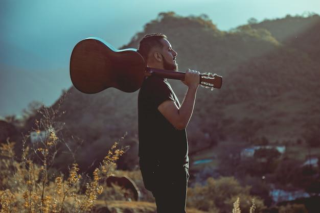 Homem, segurando, violão, montanhas