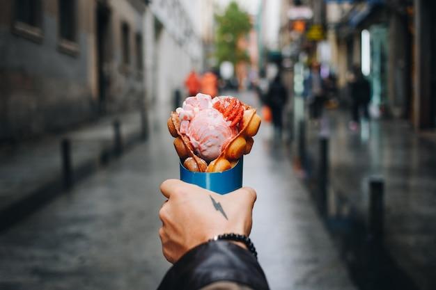 Homem segurando waffle de bolha de caminhão de comida de rua