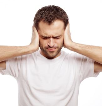 Homem segurar as mãos nas orelhas das têmporas, conceito de homem estressado, dor de cabeça, deprimido, dor, olhos fechados, usar camiseta branca, isolado no branco.