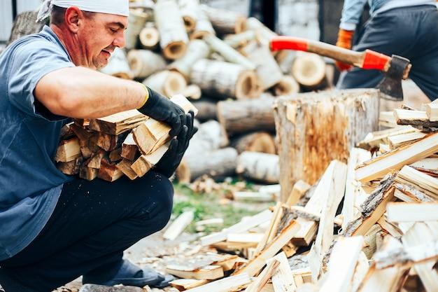 Homem segurar lenha, ele coloca madeira de corte em pilha de madeira woodpile
