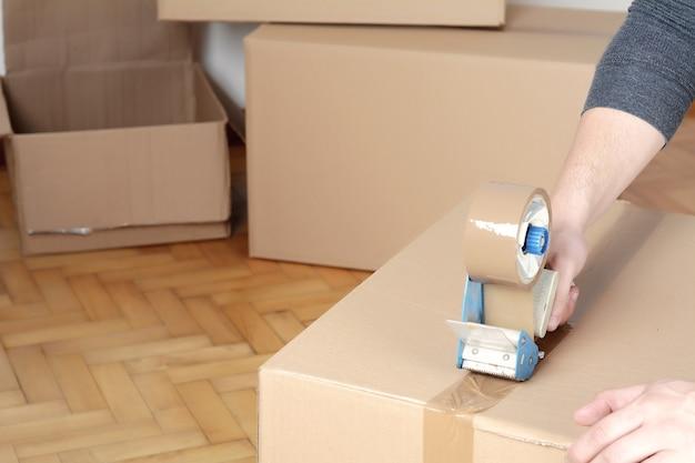 Homem, selando, um, despacho, caixa papelão