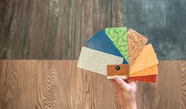 Homem seleciona a decoração de cores novos pisos de diferentes amostras coloridas em uma loja de móveis e pisos