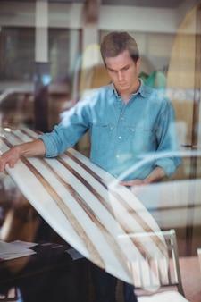 Homem selecionando prancha de surf