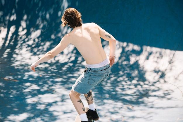 Homem sem camisa andando no skatepark