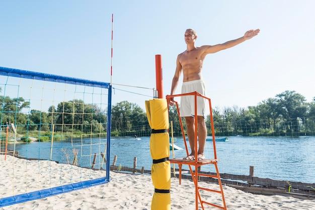 Homem sem camisa atuando como árbitro de uma partida de vôlei de praia