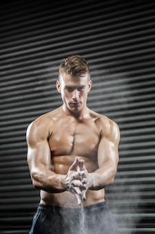 Homem sem camisa, batendo palmas de mãos com talco no ginásio crossfit