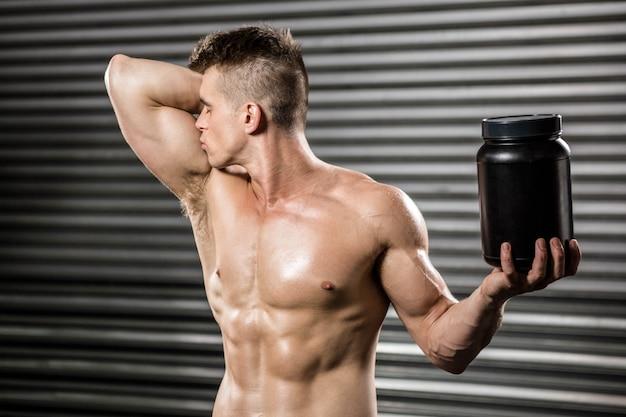 Homem sem camisa beijando bíceps e segurando pode no ginásio