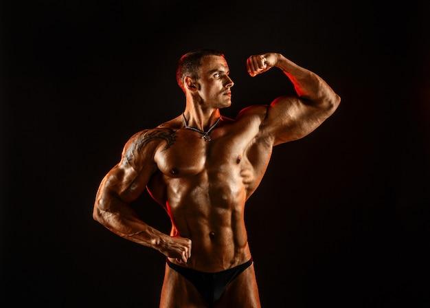 Homem sem camisa com corpo musculoso em topless, segurando o braço.