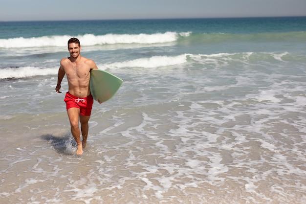 Homem sem camisa com prancha andando na praia ao sol