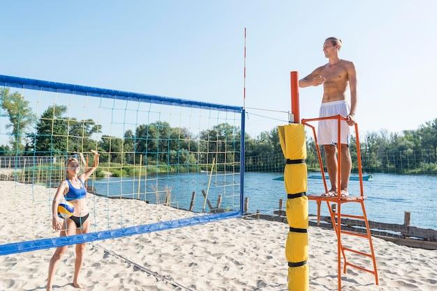 Homem sem camisa como árbitro de uma partida de vôlei de praia com uma jogadora