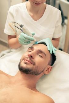 Homem sem camisa deitado de olhos fechados e esteticista cuidadosa nutrindo a pele da testa