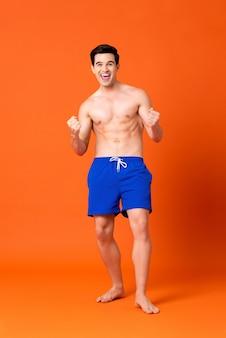 Homem sem camisa em êxtase em calças curtas azuis sorrindo e cerrando os punhos