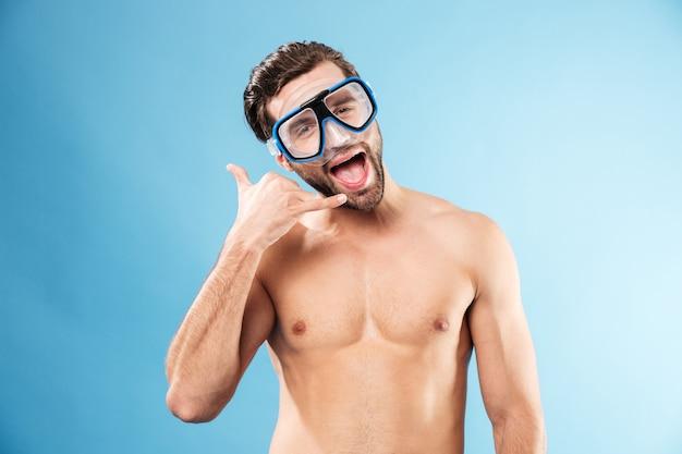 Homem sem camisa engraçado na máscara de natação, mostrando o gesto do tubo de telefone