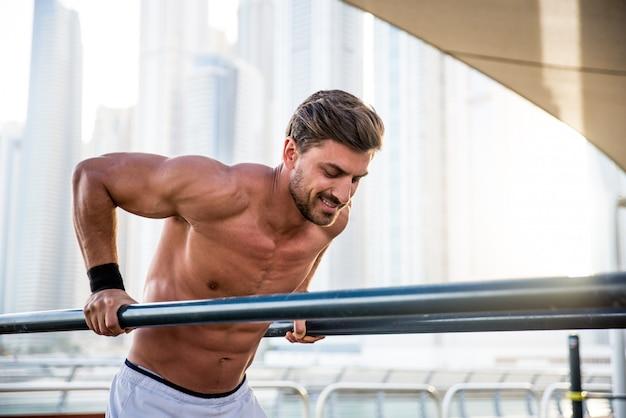 Homem sem camisa, fazendo exercícios com barras