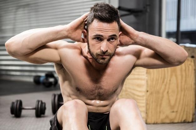 Homem sem camisa fazendo flexões abdominais no ginásio crossfit