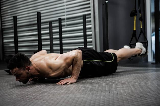 Homem sem camisa fazendo push-up com a corda no ginásio crossfit