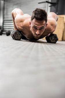 Homem sem camisa fazendo push-up com halteres no ginásio crossfit