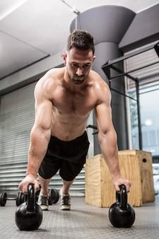 Homem sem camisa fazendo push-up com kettlebells no ginásio crossfit
