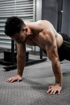 Homem sem camisa fazendo push-up no ginásio crossfit