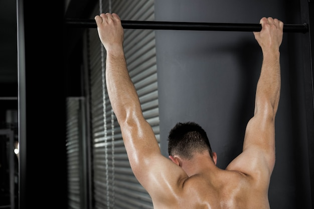 Homem sem camisa fazendo puxar para cima no ginásio crossfit