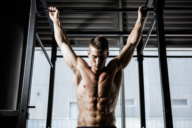 Homem sem camisa fazendo puxar para cima no ginásio