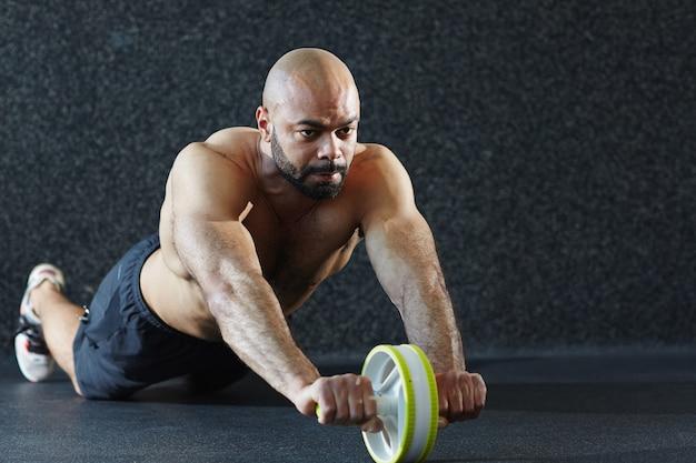 Homem sem camisa forte malhando na academia