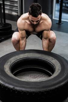 Homem sem camisa, lançando pneus pesados no ginásio crossfit