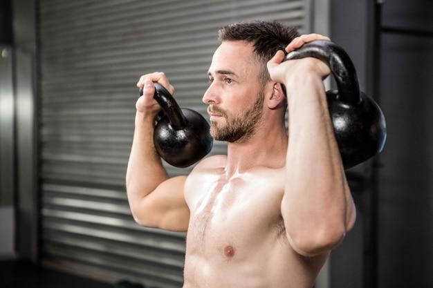 Homem sem camisa levantamento kettlebells no ginásio crossfit