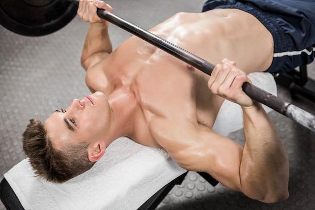 Homem sem camisa, levantando a barra pesada no banco no ginásio