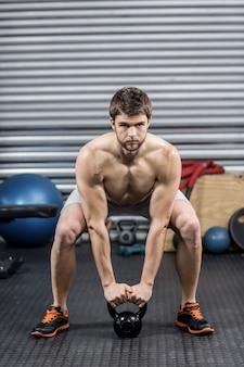 Homem sem camisa, levantando halteres no ginásio crossfit